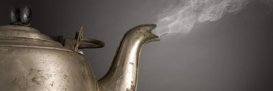 Old alluminum kettle steaming (or smoking) on gray vignette background
