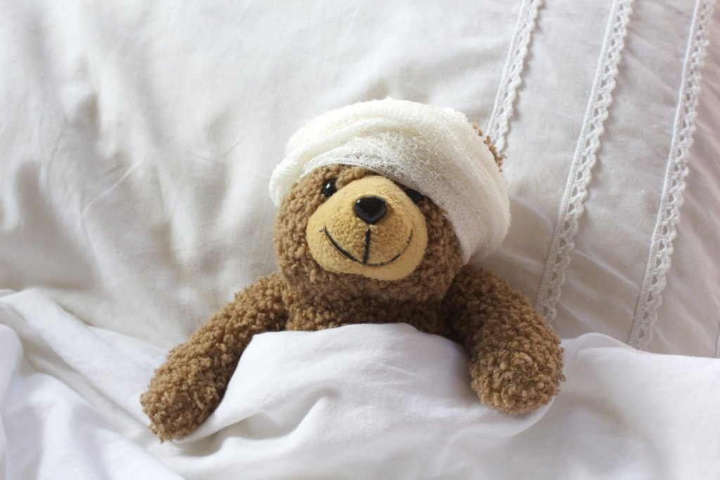 Landscape shot of a poorly teddy resting in bed